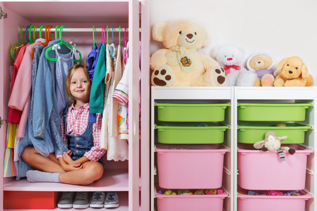 A little child girl is sitting in a wardrobe in a children's room. Saving and storage system for children's things and toys concept.