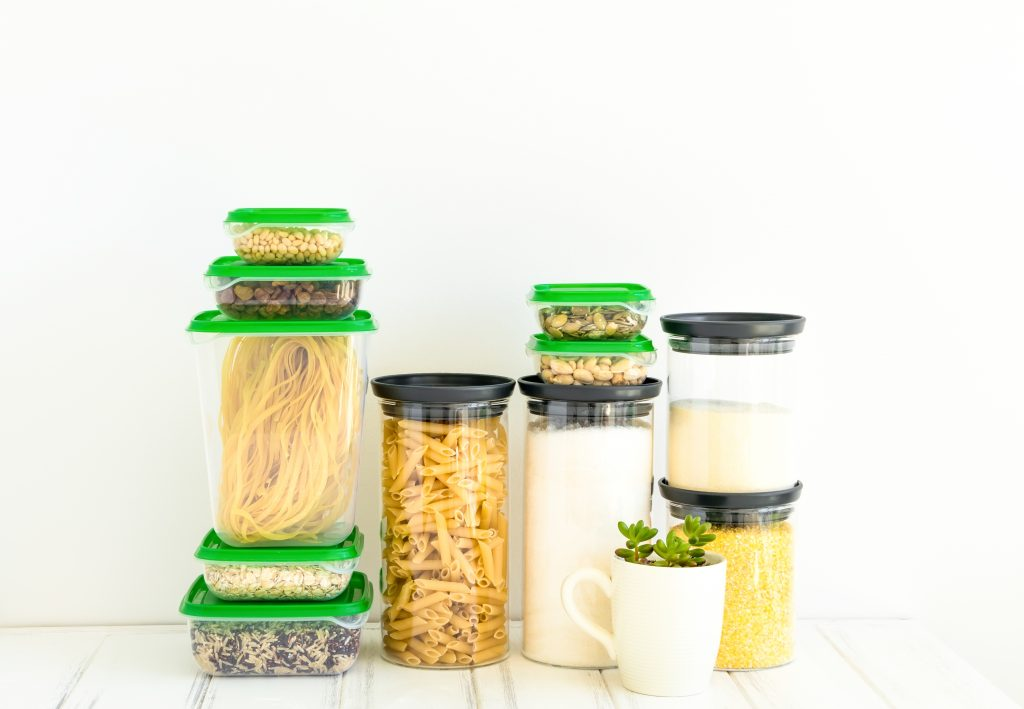 Pasta and cereals in glass and plastic jars on white background. Organized kitchen and healthy eating concept